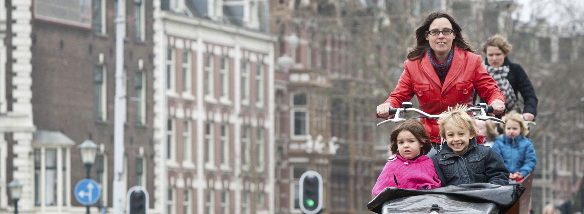 Moeder fietst door Amsterdam met kind in bakfiets.